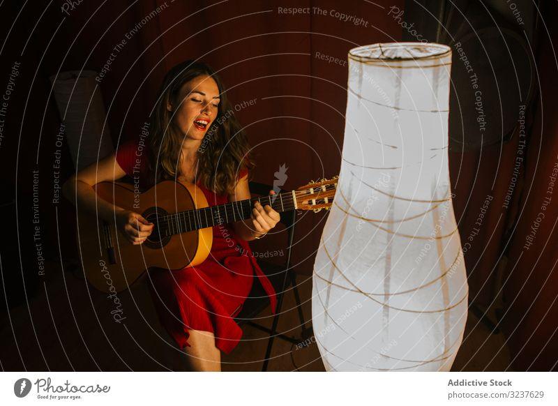 Frau singt und spielt Gitarre auf der Bühne bei Lampenlicht Sänger Leistung Musik Musiker Gitarrenspieler Schauplatz Konzert sinnlich Entertainment Gesang Klang