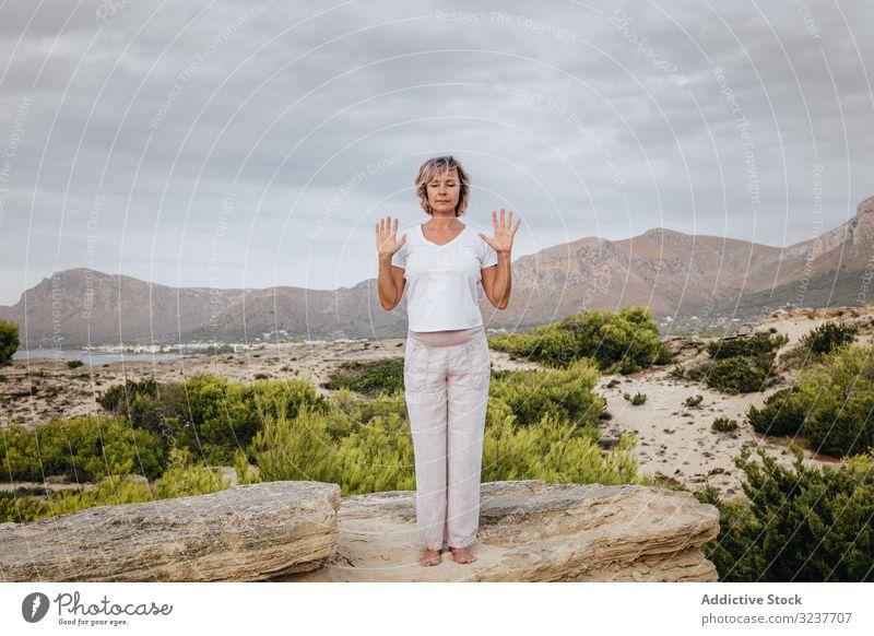 Barfüßige Frau meditiert auf Stein Meditation Übung Felsen Tai Chi geschlossene Augen Natur Himmel wolkig Training Erwachsener Barfuß Atem Gesundheit passen