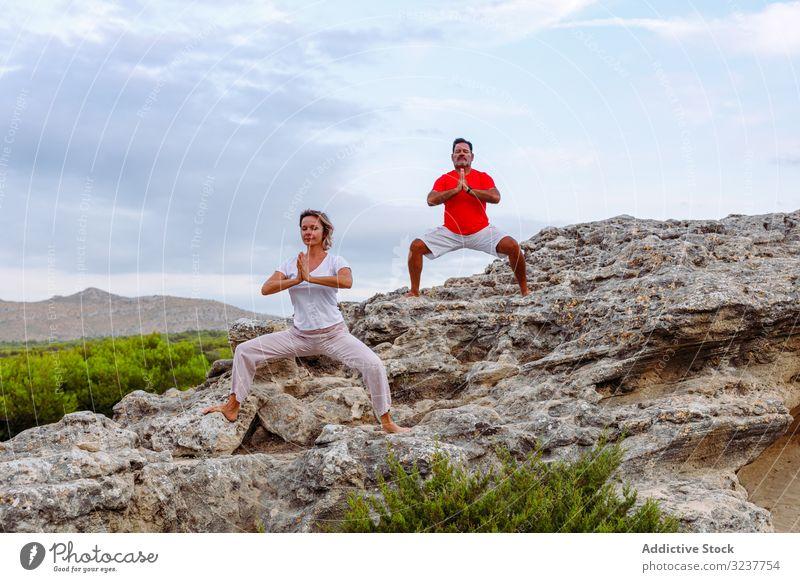 Paar meditiert auf Felsen Meditation Atem Übung Tai Chi umklammerte Hände geschlossene Augen Natur Himmel wolkig Training Frau Mann Erwachsener Gesundheit