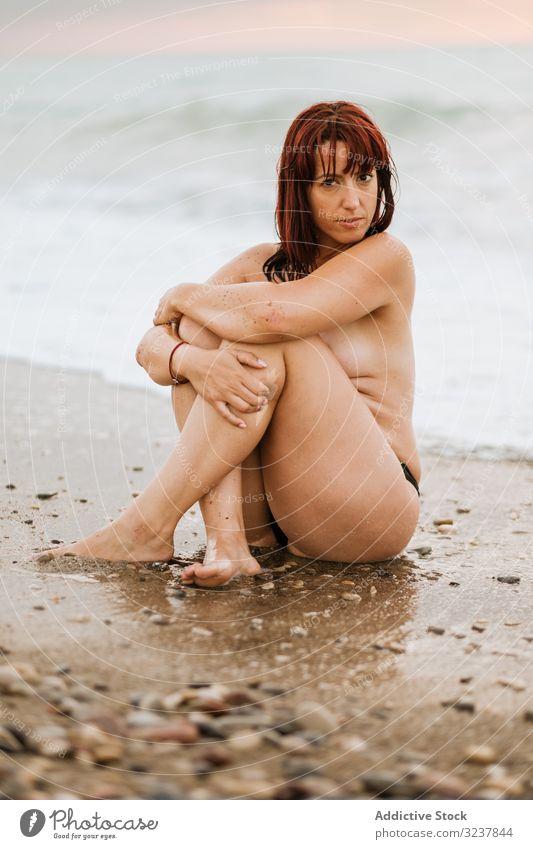 Nackte Frau sitzt in der Nähe von Meereswellen nackt MEER erotisch sexy sinnlich frei verführerisch oben ohne Eleganz Brust Körper Haut entkleidet unbedeckt