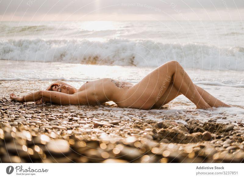Nackte Frau in der Nähe von Meereswellen liegend nackt MEER erotisch sexy sinnlich frei verführerisch oben ohne Eleganz Brust Körper Haut entkleidet unbedeckt
