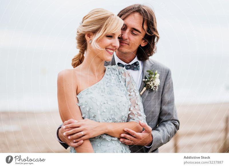 Glückliches junges Ehepaar verbringt gemeinsam Zeit am Meer striegeln Braut Hochzeit Heirat Liebe Feier Paar Ehefrau Frau Fröhlichkeit heiter umarmend