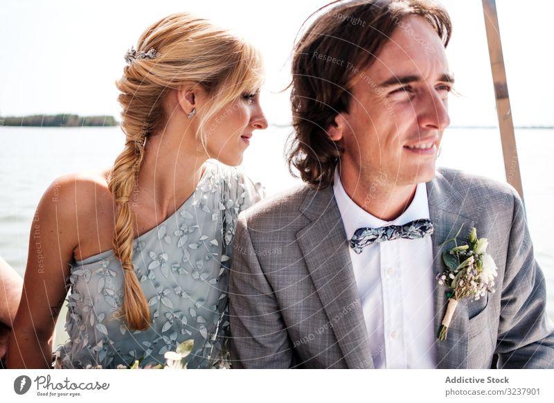 Paar hält sich beim Sitzen auf dem Boot an den Händen striegeln Braut Hochzeit Heirat Liebe Feier Ehefrau Frau Fröhlichkeit heiter umarmend Partnerschaft