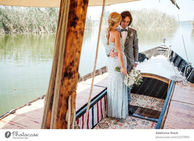 Paar hält auf dem Boot Händchen striegeln Braut Hochzeit Heirat Liebe Feier Ehefrau Frau Fröhlichkeit heiter umarmend Partnerschaft Jungvermählter Natur