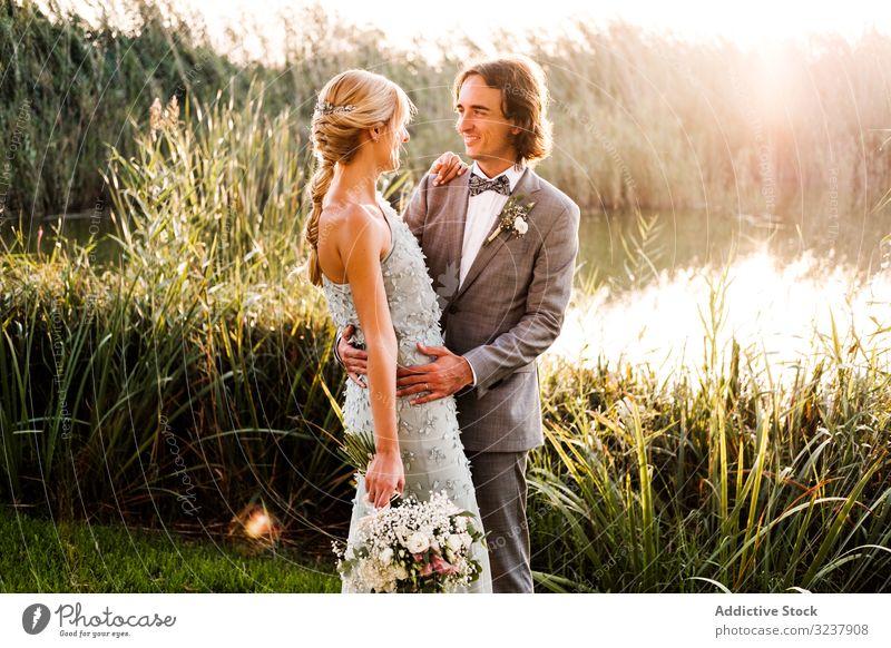 Glückliches frisch verheiratetes Paar erfreut sich an Naturereignissen striegeln Braut Hochzeit Heirat Liebe Feier Ehefrau Frau Fröhlichkeit Küssen Pflanzen