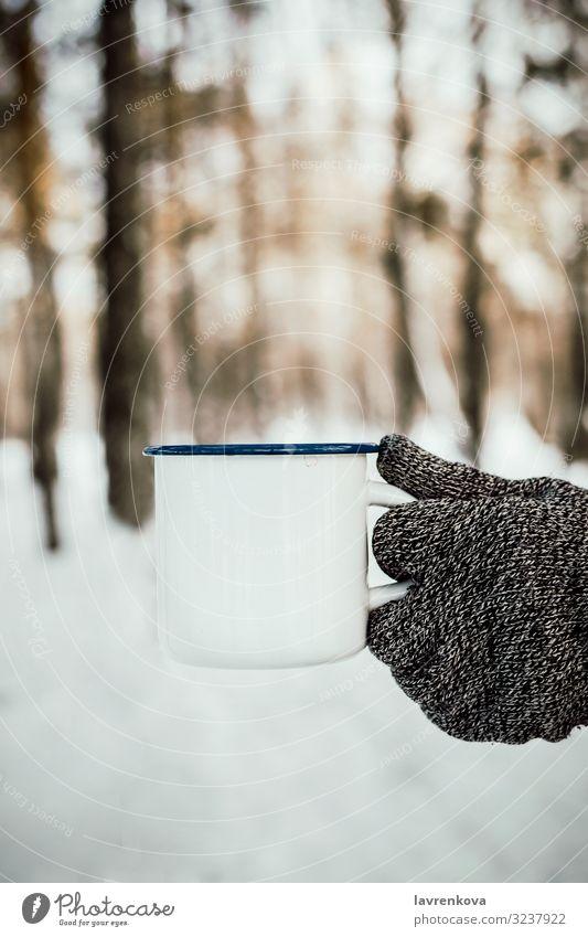 Männerhand im Strickhandschuh mit weißem Emailbecher Jahreszeiten kalt Erkältung Handschuhe gestrickt Natur frisch Morgen Holz Wald Außenaufnahme vertikal