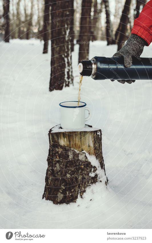 Männerhand, die Heißgetränk in eine Email-Tasse gießt. Thermosflasche Hintergrund Getränk braun Kaffee kalt trinken Wald frisch Handschuhe wandern heiß