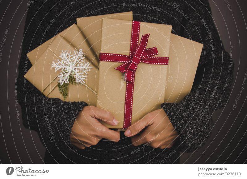 Frau mit dunklem Pullover, die viele Weihnachtsgeschenke hält. schwarz Buch Kasten Weihnachten & Advent Claus Zusammensetzung Handwerk dunkel festlich Tanne
