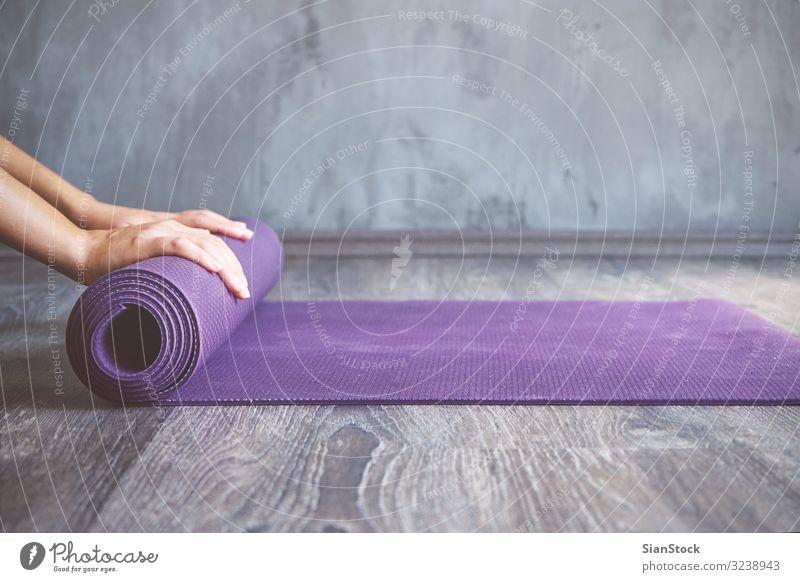 Frau rollt ihre Matte nach einem Yoga-Kurs Lifestyle schön Körper Erholung Meditation Sport Mensch Erwachsene Fitness dünn jung üben Pose Training Gesundheit