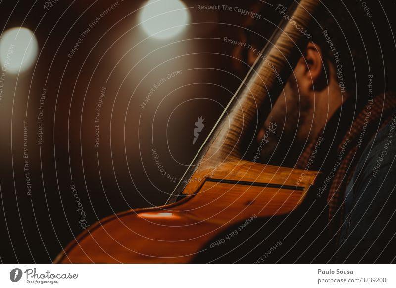 Cello spielender Mann Musik Schauplatz Orchester Konzert Farbfoto Musiker Musik hören Detailaufnahme Innenaufnahme Kunst Kunstlicht Textfreiraum Nahaufnahme