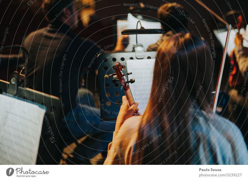 Rückansicht einer Frau mit Violine Geige Geiger Orchester Schauplatz Musik Musikinstrument Musiker Konzert Farbfoto Nahaufnahme Streichinstrumente Innenaufnahme