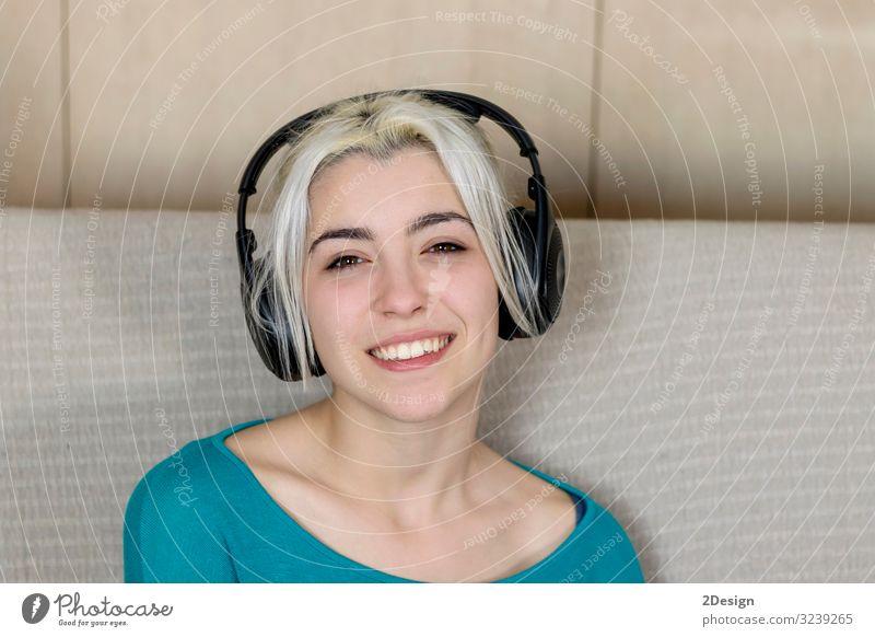 Nahaufnahme einer lächelnden jungen Frau mit Kopfhörern, während sie auf dem Sofa sitzt und in die Kamera schaut Lifestyle Glück schön Gesicht Erholung