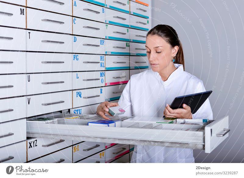 Apothekerin, die neben Medikamentenregalen steht und Tabletten hält Glück schön Krankheit Azubi Labor Arbeit & Erwerbstätigkeit Beruf Technik & Technologie