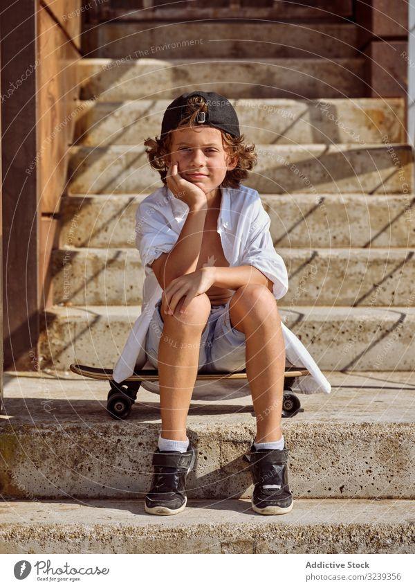 Kind sitzt auf einer Treppe im Skatepark Junge Skateboard Stil Sitzen heiter Glück Lifestyle Holzplatte ruhen auf die Hand gestützt Sport Freizeit Hobby jung