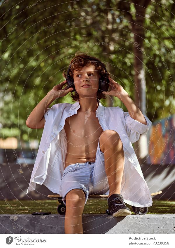 Junge mit Kopfhörern entspannt sich im Skatepark Kind Lifestyle sich[Akk] entspannen besinnlich cool Interesse Anfänger träumen Sport Freizeit Hobby jung