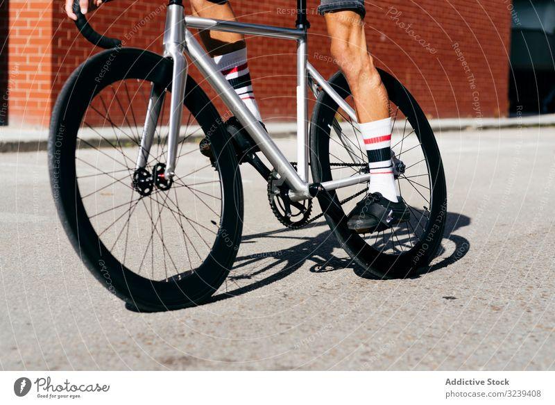 Sportlicher Mann fährt Fahrrad neben Ziegelmauer Backsteinwand Mitfahrgelegenheit modern Reiten sportlich aktiv Sommer männlich gutaussehend Radfahrer Erholung