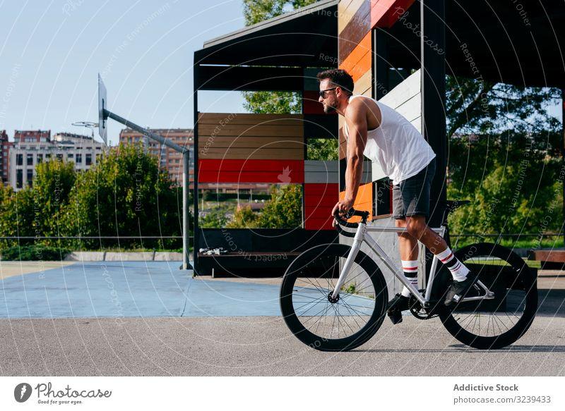 Mann fährt Fahrrad neben Gebäuden Mitfahrgelegenheit Brücke Großstadt modern aktiv sportlich Sommer männlich Sonnenbrille Radfahrer Erholung Gesundheit