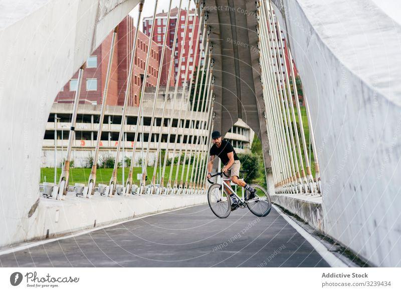 Mann fährt Fahrrad auf Fußgängerbrücke Großstadt Mitfahrgelegenheit Brücke modern aktiv sportlich Sommer männlich Erwachsener Verschlussdeckel Radfahrer