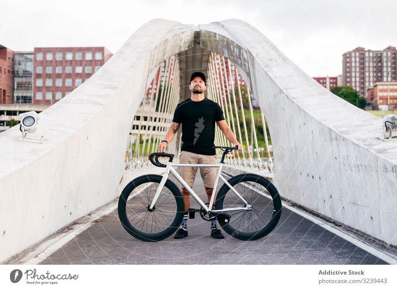 Fröhlicher Mann mit Fahrrad auf Steg stehend Großstadt Mitfahrgelegenheit Brücke modern aktiv sportlich Sommer männlich Erwachsener Glück heiter Lächeln