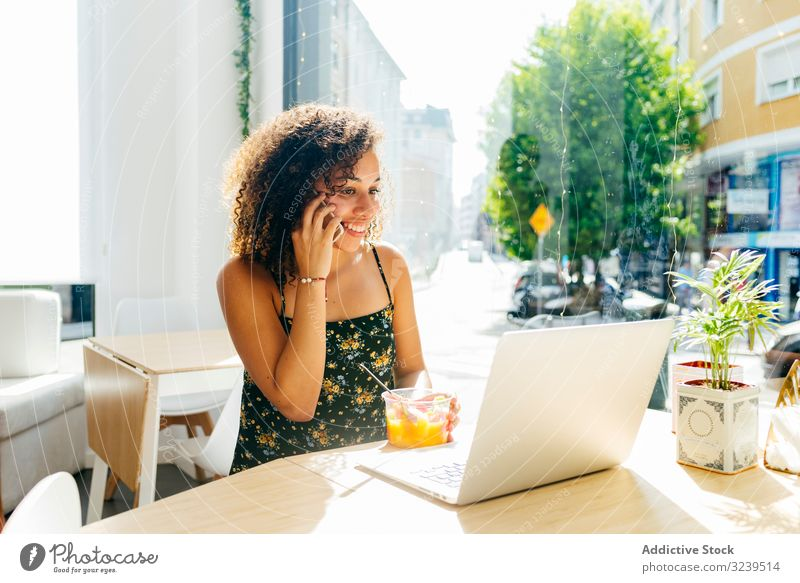 Ethnische Frau mit Laptop genießt gesundes Getränk im Café benutzend trinken Gesundheit Saft ethnisch Tisch Fenster sitzen Lifestyle ruhen sich[Akk] entspannen
