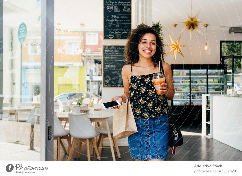 Fröhliche ethnische Frau verlässt Restaurant Café trinken Gesundheit Lächeln Smartphone Tüte lassen urban Vitamin Getränk Saft Smoothie Tasse Entzug heiter
