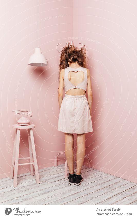 Rückenansicht eines jungen Mädchens Telefon Wand Lampe im Innenbereich rosa unzufrieden lange Haare wütend passiv Stehen unglücklich Frisur Verlust Stress