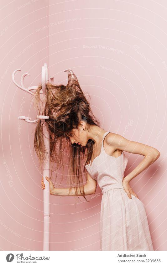 Teenager-Mädchen mit verfilzten Haaren Kleiderständer im Innenbereich rosa verärgertes Mädchen frustrierte Frau wütende Frau Single Schwierigkeiten Nervös