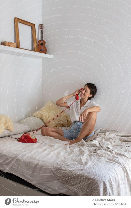 Fröhliche Frau im Telefongespräch Gespräch Lächeln Bett zuhören Dialog Anruf Schlafzimmer Wand sitzen heimwärts Appartement flach retro altehrwürdig Mitteilung