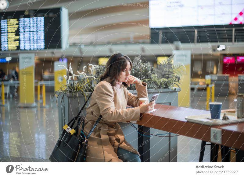Dame sitzt und benutzt Smartphone am Flughafen Frau Warteraum Flugzeug Abheben benutzend Reisender Kaffee Telefon Browsen Terminal Mobile zuschauend Surfen