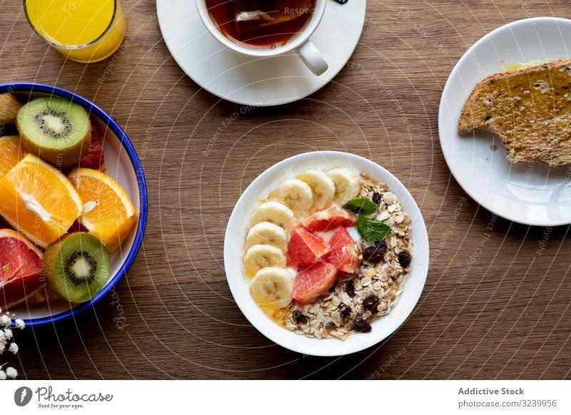 Saft und Teller mit Müsli und Früchten auf dem Tisch Frucht Büffet Mahlzeit aufgeschnitten Zitrusfrüchte Frühstück Erdbeeren Banane Tee Gesundheit orange