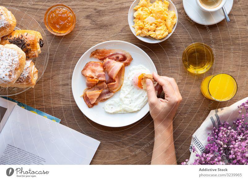 Person liest beim Essen von Speck und Eiern bei Tisch Frühstück Buch Eigelb Wahl Dip lesen Sortiment Lebensmittel Buffet Büffet Mahlzeit Ernährung gebraten