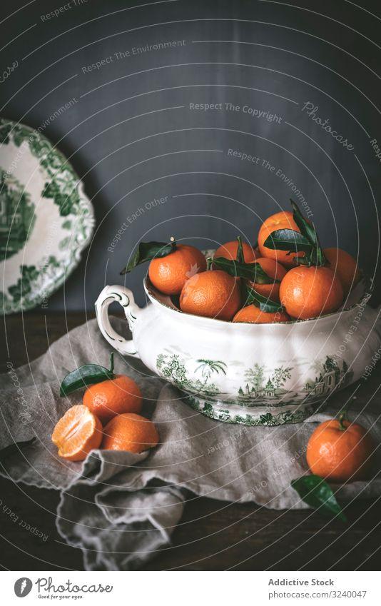 Orangefarbene Mandarinen in Keramik-Ornamentschale auf Holztisch anspruchsvoll Frucht Gesundheit klassisch Schalen & Schüsseln Zusammensetzung Stillleben Kunst