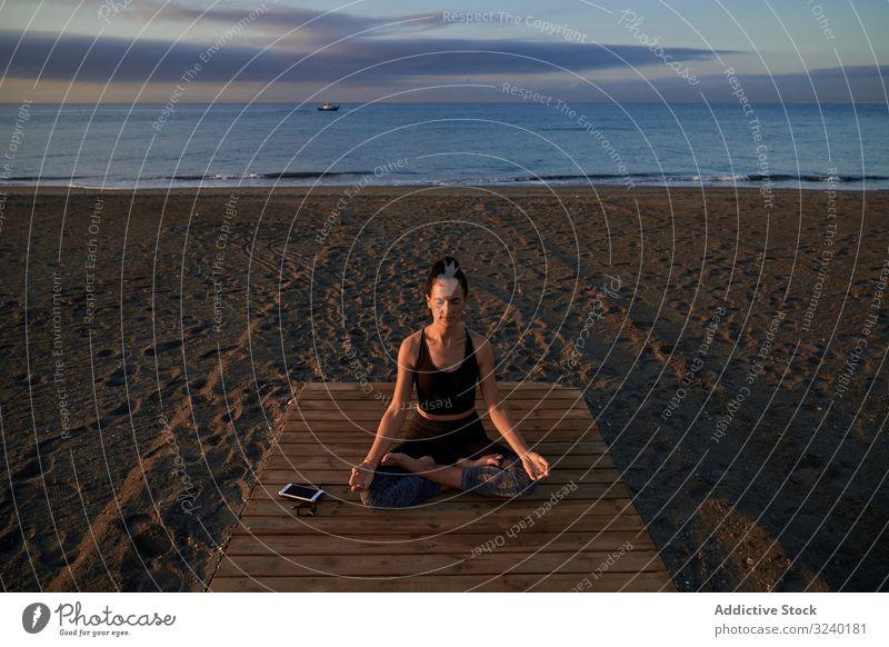 Barfüssige Frau meditiert auf Holzpfad Yoga Strand Asana Aktivität Lotus-Pose passen geschlossene Augen gekreuzte Beine Weg schlank Sportbekleidung Training