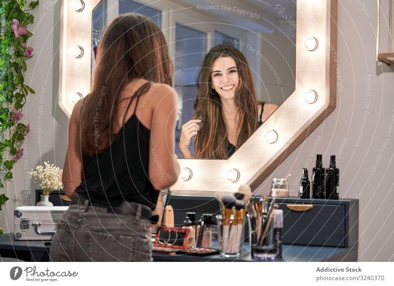 Lächelnde Frau betrachtet Spiegel in der Hand im Kosmetiksalon Reflexion & Spiegelung Salon Make-up Pflege Behandlung Gerät Stil bequem Schönheit Innenbereich