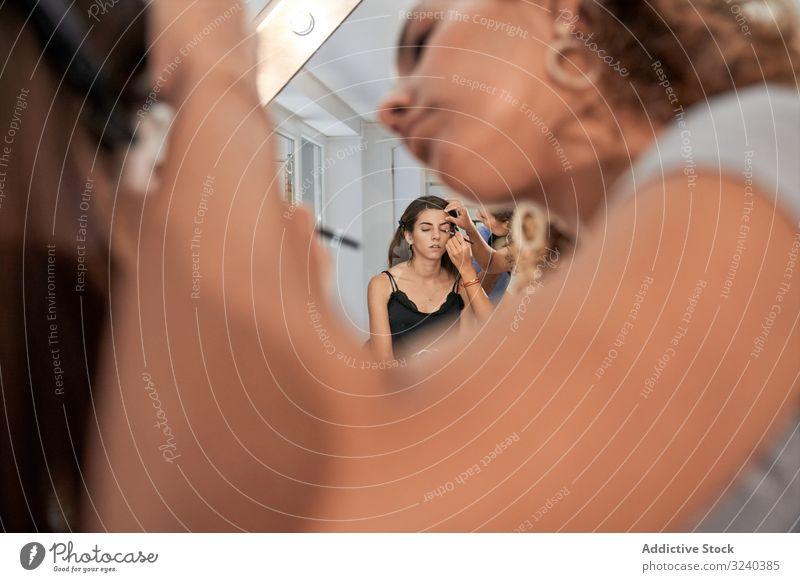 Maskenbildner malt Gesicht einer ruhigen Frau Make-up Malerei Künstler Auge Schönheit Kosmetik Stylist Salon Pflege Behandlung Stil bequem Zeichnung anwendend