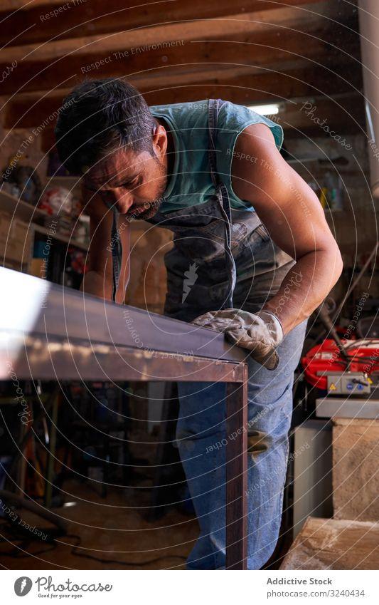 Mann arbeitet mit Metall in der Werkstatt Mark Präzision Arbeit Gerät Werkzeug Herstellung Genauigkeit Stahl Technik & Technologie Beruf Inszenierung