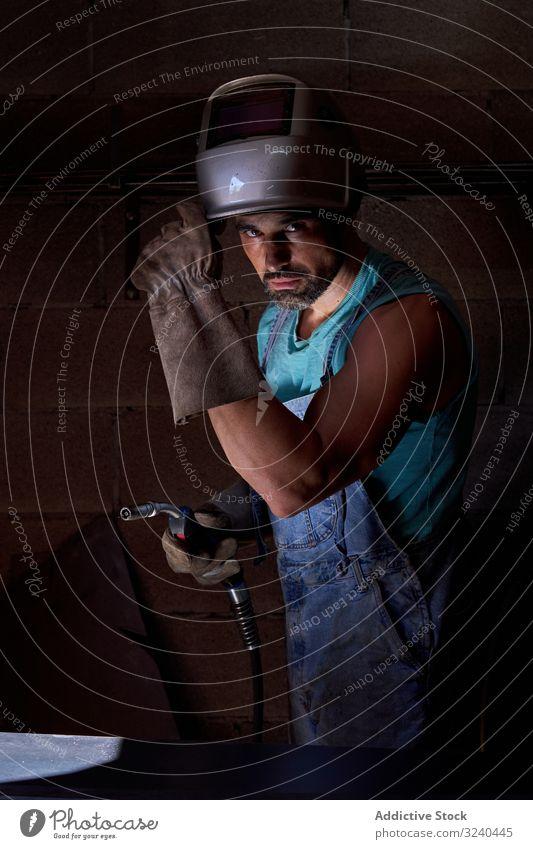 Arbeiter, der Lötwerkzeuge für die Verwendung von Mann Porträt Schweißer Handwerker ernst selbstbewusst Kunsthandwerker löten Schlosserin Latzhose