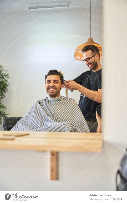 Spiegelung im Spiegel eines Klienten, der lacht, während der Friseur ihm die Haare mit einem Rasiermesser schneidet Dienst Fröhlichkeit Lächeln Hände Reflexion