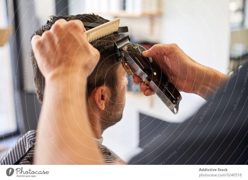 Detail der Hände eines Friseurs, der die Haare mit einem Kamm und einem Rasiermesser schneidet Detailaufnahme Rasierapparat geschnitten Barbershop Frisur Arbeit