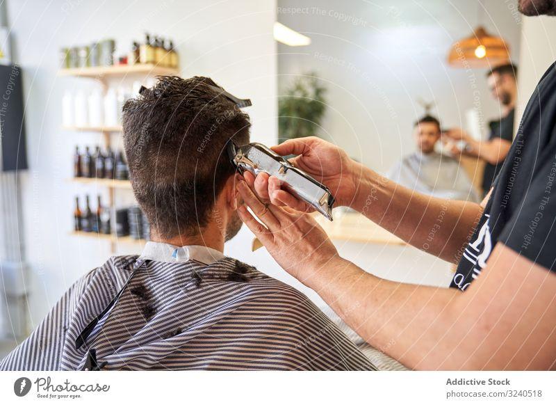 Rücken eines Kunden in einem Friseurladen, der auf einem Stuhl sitzt und sich die Haare schneidet Dienst Hände Spiegel Reflexion Rasierapparat geschnitten
