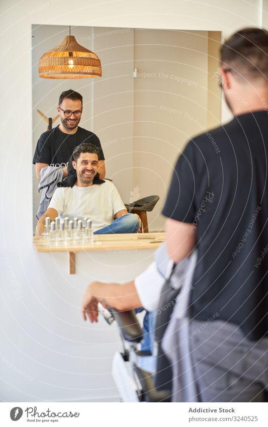 Vertikales Foto eines Friseurs, der einem Kunden vor einem Spiegel mit einem Handtuch die Haare trocknet vertikal Saloon Stuhl Produkte Barbershop Trocknung