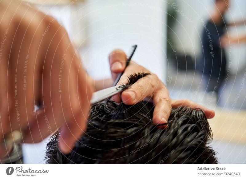 Detail einer Hand von einem Friseur, der einem Kunden mit Schere und Kamm die Haare schneidet Haarschnitt Salon Klient Haarpflege menschlich Barbershop Pflege