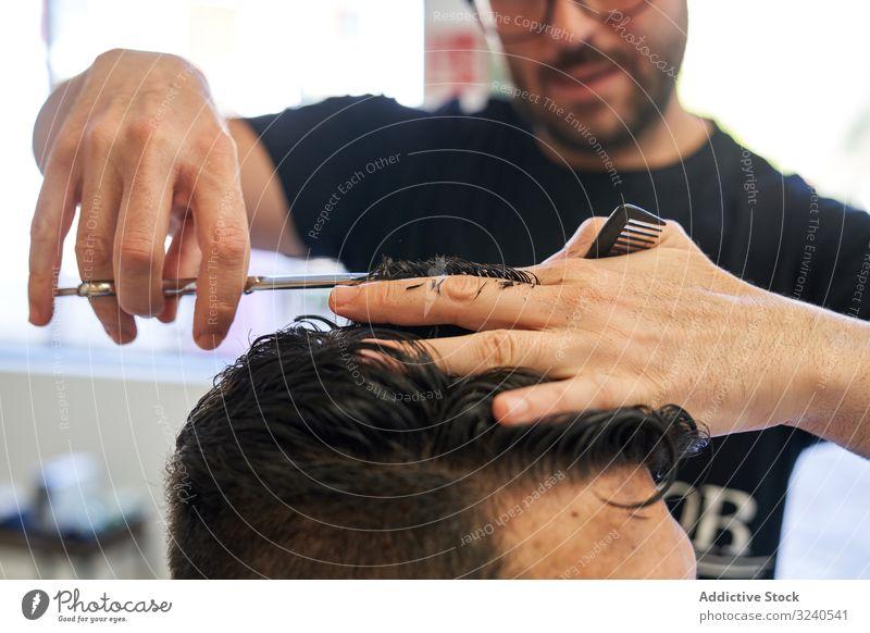 Detail einer Hand von einem Friseur, der einem Kunden mit Schere und Kamm die Haare schneidet, mit der Unschärfe im Hintergrund geschnitten Haarschnitt Salon