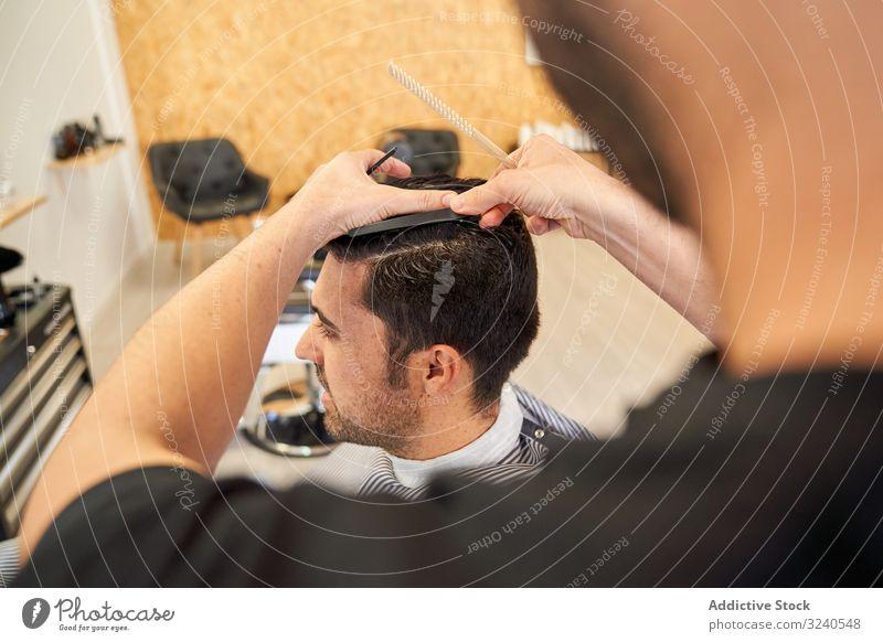 Friseur schneidet einem Kunden die Haare im Sitzen auf der Friseurcouch geschnitten Barbershop Kamm Frisur Möbel Arbeit Dienst professionell Hände Waffen nass