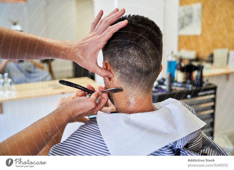 Detail der Hände eines Friseurs, der einem Kunden mit einem Rasiermesser die Haare schneidet Rasierer handgefertigt altehrwürdig Nacken Dienst Spiegel Reflexion