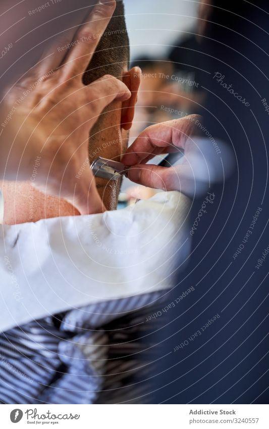 Vertikales Foto eines Ausschnitts der Hände eines Friseurs, der einem Kunden mit einem Rasiermesser die Haare schneidet vertikal Rasierer handgefertigt