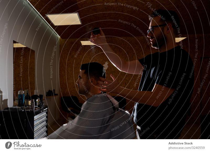 Friseur kämmt und verteilt Schönheitsprodukte an eine Kundin Schwarzlicht Licht Silhouette Aufstrich Kamm Endbearbeitung Produkt Dienst Hände Rasierapparat