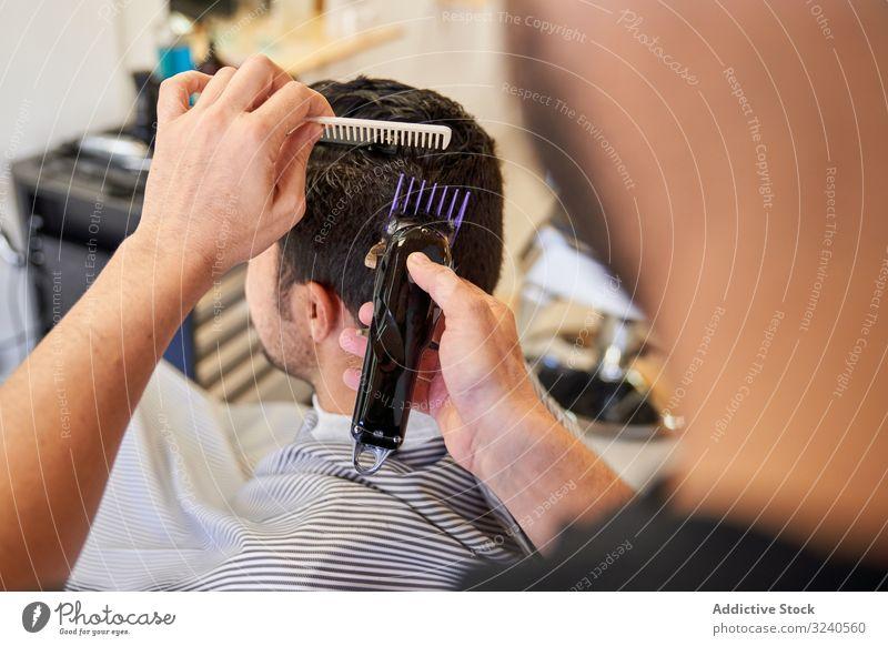 Friseur, der einem Kunden, der auf dem Friseurstuhl sitzt, mit einer Maschine Haare schneidet Rasierapparat geschnitten Barbershop Kamm Frisur Möbel Arbeit