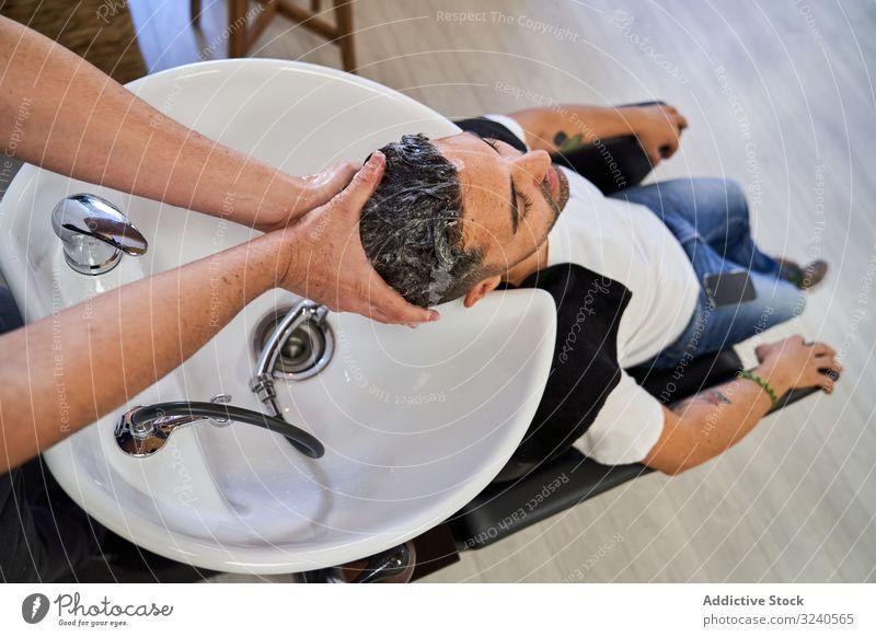 Friseur, der den Kopf mit Shampoo wäscht, an einen Kunden, der mit dem Kopf auf dem Waschbecken liegt Haarwaschmittel Abschaum Sauberkeit Produkte Kosmetik