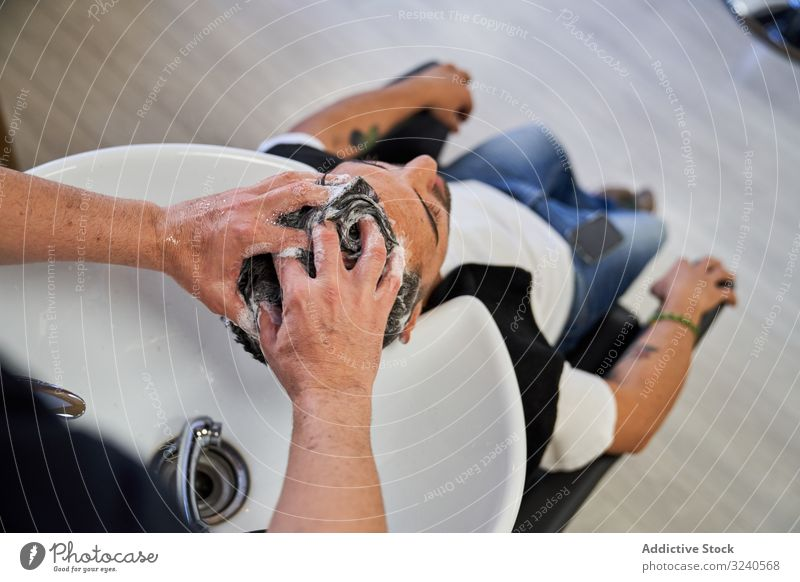 Hände eines Barbiers, der einem Kunden den Kopf mit Shampoo wäscht, wobei der Kopf auf dem Waschbecken ruht Detailaufnahme Haarwaschmittel Abschaum Sauberkeit